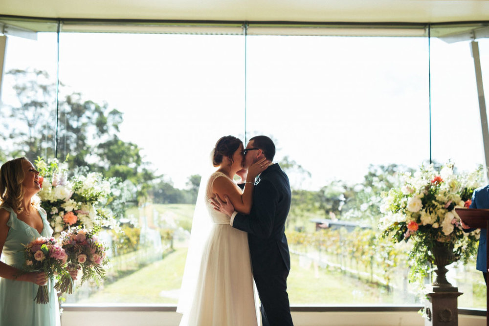bride and groom kissing in front of window