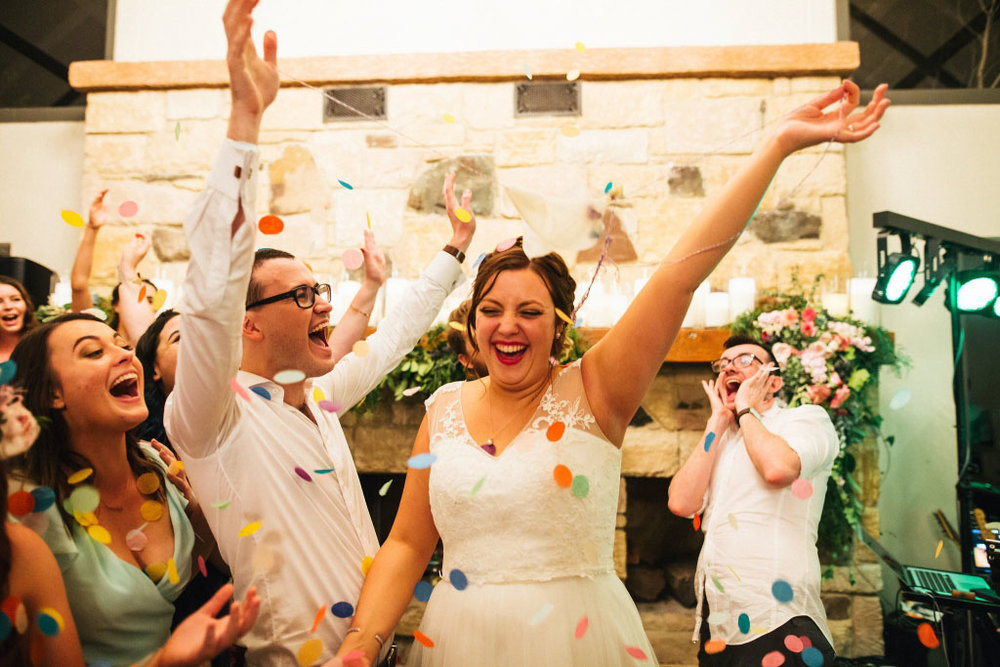 Bride and groom party and dance with their guests confetti in the air