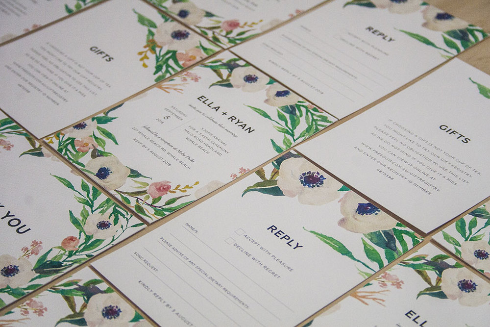 Invitation suite with white flowers and greenery