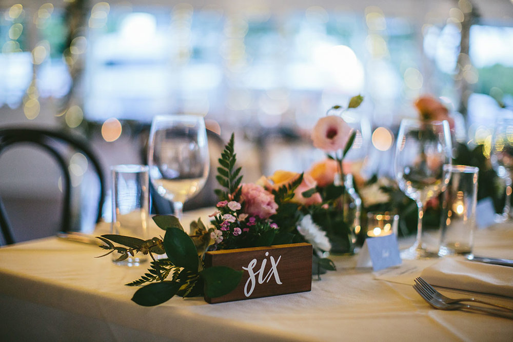 Wedding at Salsa Restaurant in Port Douglas Floral table arrangements and navy place cards