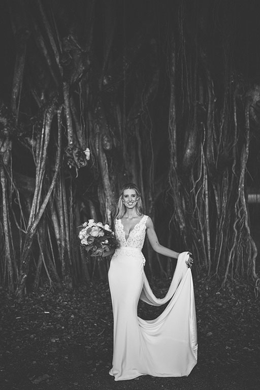 Bride standing in front tree trunks in Port Douglas with bouquet in white wedding gown