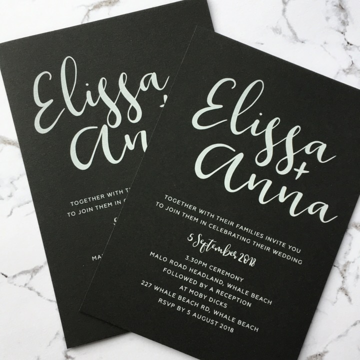 White ink printed on black card wedding invitation calligraphy