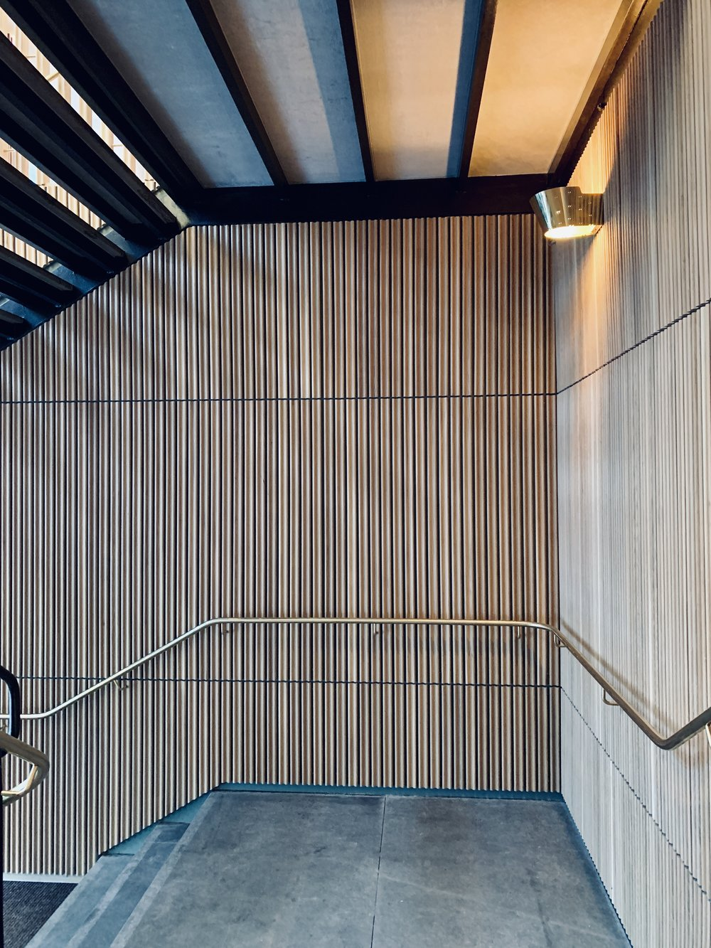 Restaurant Tivander architect drawn concrete staircase, brass hand railing and lighting