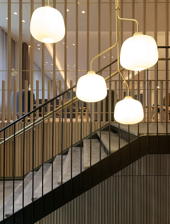 Restaurant Tivander architect drawn concrete staircase, brass hand railing and lighting, chandelier