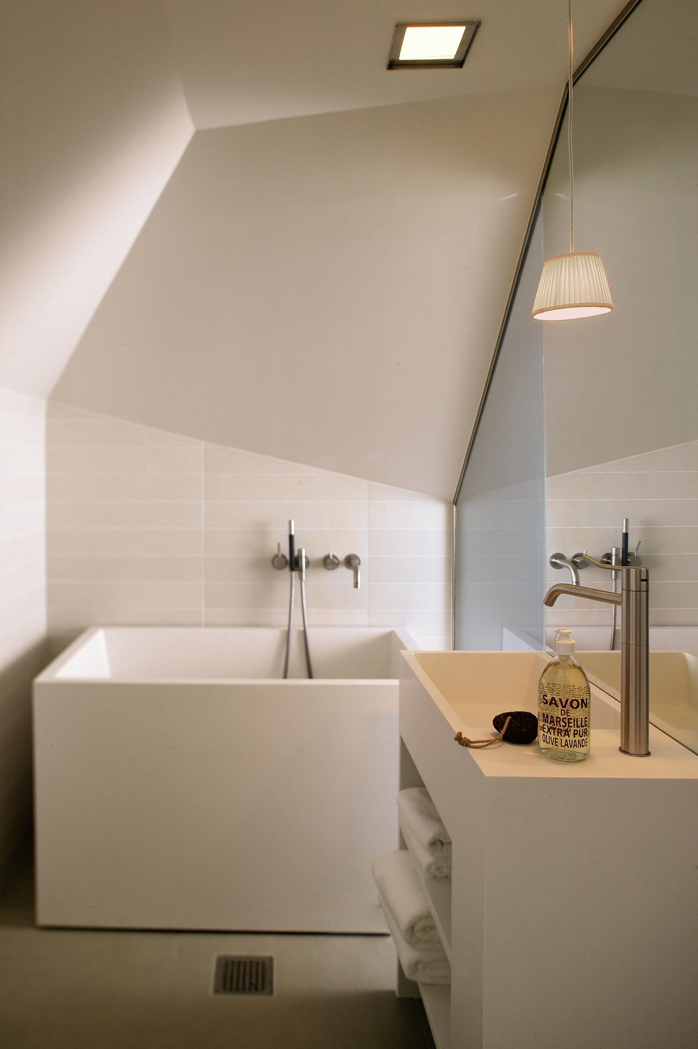 Hotel Brosundet Ålesund Norway, hotel room, modern and sharp bathroom with cream tiles and frosted glass, interior design by GARDE. Mads Emil Garde