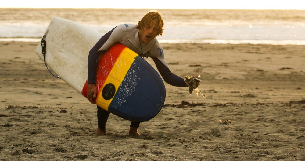 Simen Knudsen doing what he does best- surfing and picking up trash at the beach. Photo: Mads Schwencke