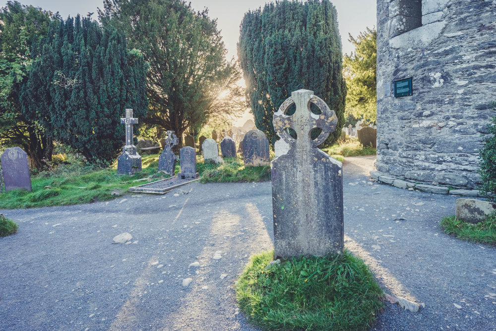 glendalough. irish history. county wicklow. round tower. hill walknig. hiking. grave yard. wildlife. tombstones. lakes. blue sky. head stones in the sun.jpg
