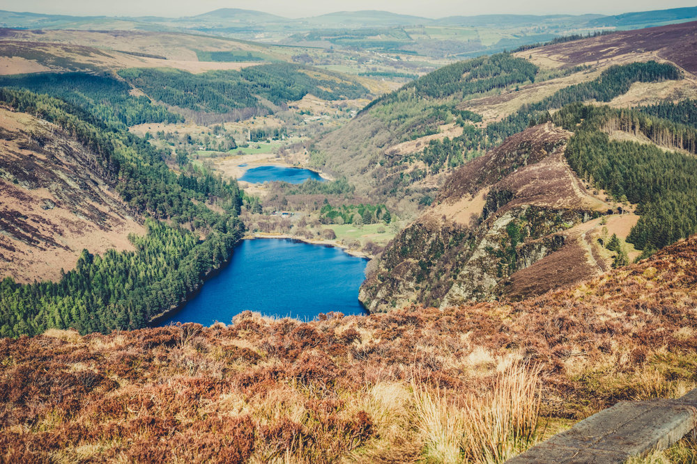 glendalough. irish history. county wicklow. round tower. hill walknig. hiking. grave yard. wildlife. tombstones. lakes. blue sky. over looking the two lake.jpg