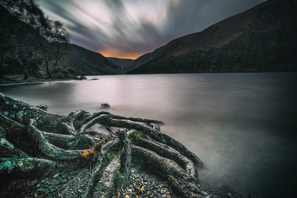 glendalough. irish history. county wicklow. round tower. hill walknig. hiking. grave yard. wildlife. tombstones. lakes. blue sky. the lower lake. sun set over the lake.jpg