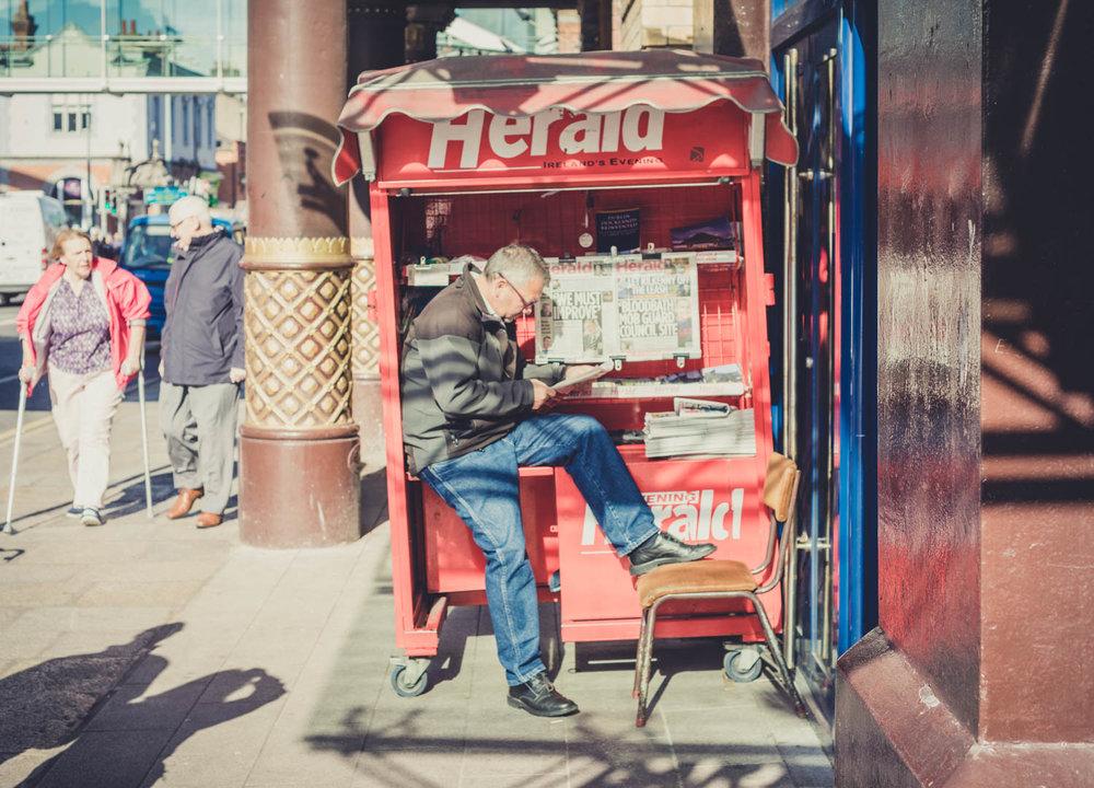 Dublin. Dublin city. street photography. ireland. travel. travel photography. photowalk. walking. people. street. art. on the street. selling the paper.jpg