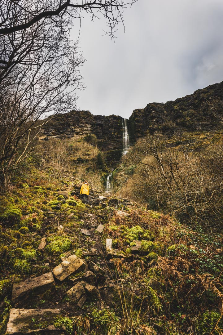 girl in yellow jacket standing under waterfall