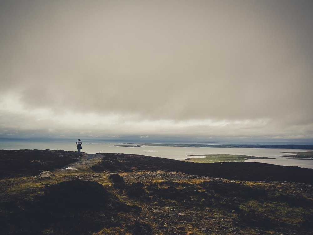 girl standing atop a large hill overlooking the wild atlantic way