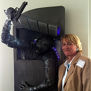 "Heather Davis with her sculpture called ""Shadow Man,"" which depicts Mitch Rapp escaping into an open from a return duct.  This sculpture won ""Best of Show"" -the award of excellence by the people's choice at Chester County (PA) Art Association Show at the Chester County Gallery last December. She gifted this piece to Vince."