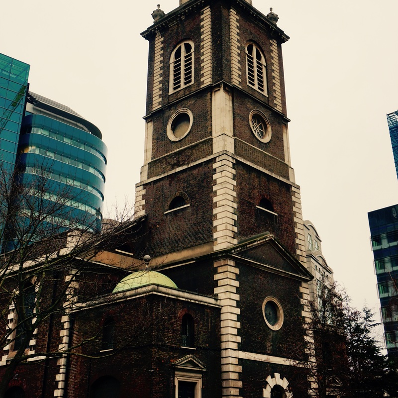 """""""Old Father Baldpate"""" say the slow bells of Aldgate...   The earliest written record of  St. Botolph's Aldgate  dates from 1115, but there may have been a church on the site from before 1066. The church was rebuilt in the 16th century, renovated in 1621 and escaped the Great Fire. The present building dates between 1741 and 1744, and was designed by George Dance the Elder. Old Father Baldpate is believed to be St. Botolph himself, with baldpate being a reference to his bald head."""