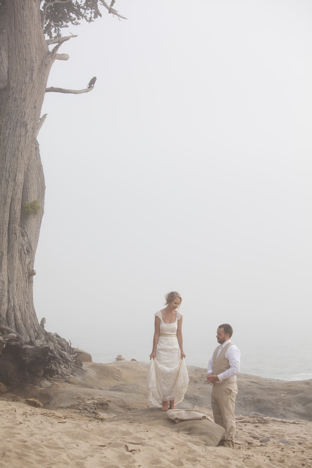The bride is standing above the groom on a rock.
