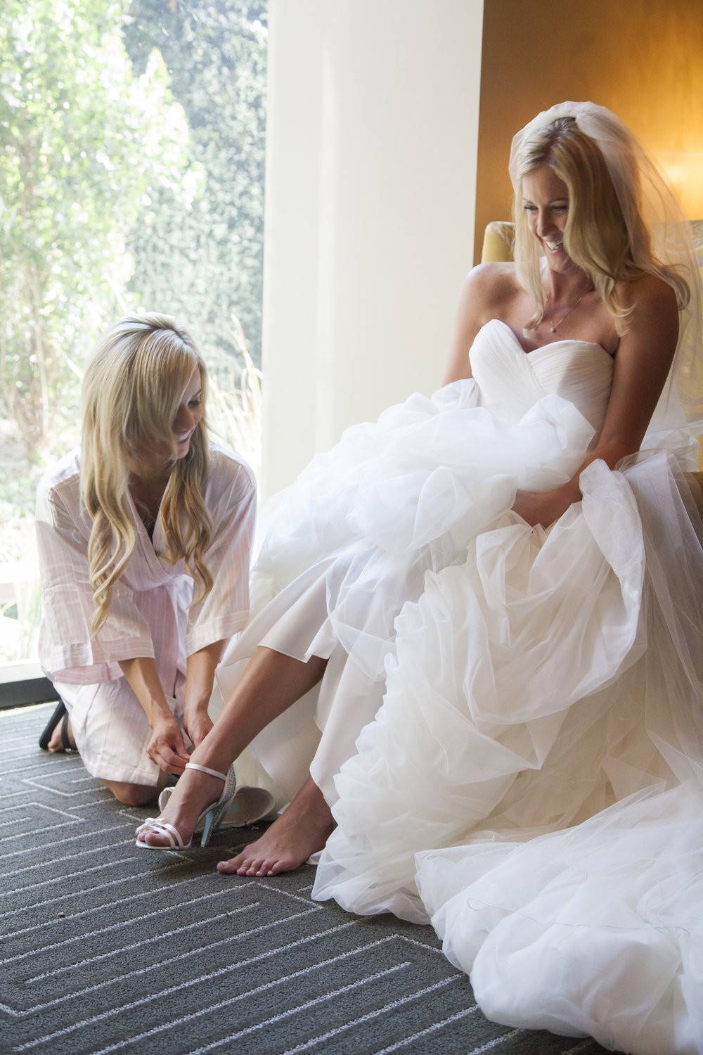 The bride's mother is helping her put on her wedding shoes.