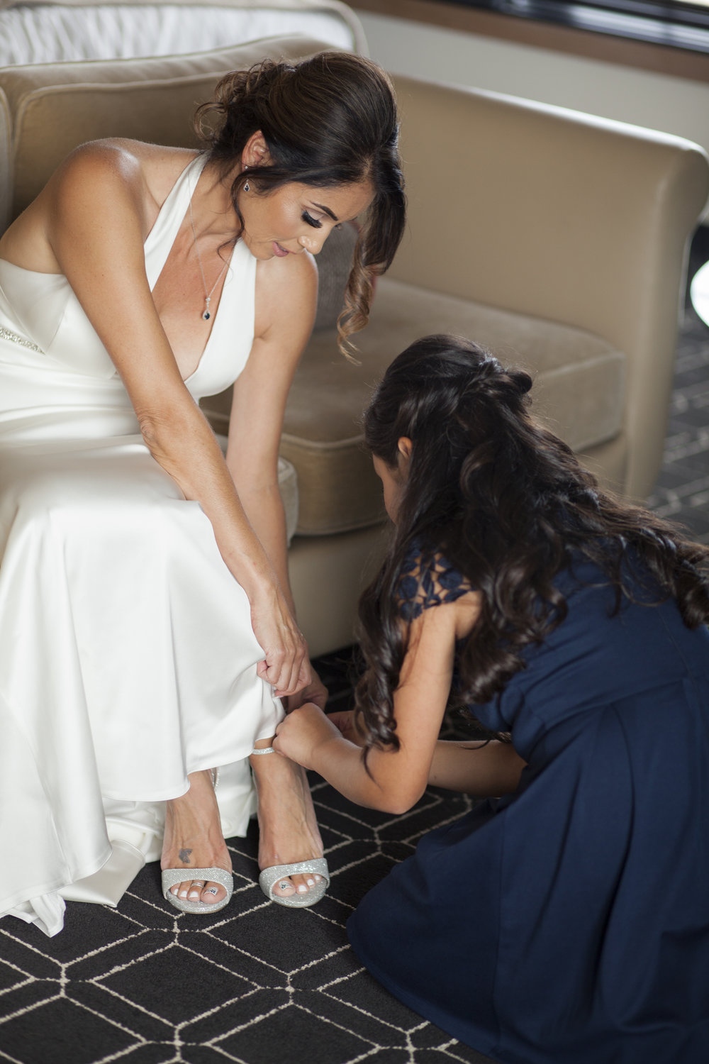 The bride is sitting on a couch, putting her shoes on.
