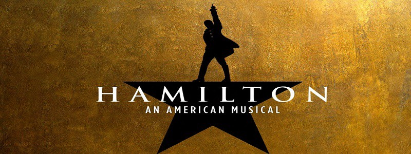 """Image description: """"Hamilton"""" logo in black on a gold background, silhouette of a 5 pointed star with the top point replaced by silhouette of a man with one arm raised. Text in white across star reads """"Hamilton"""" An American Musical."""