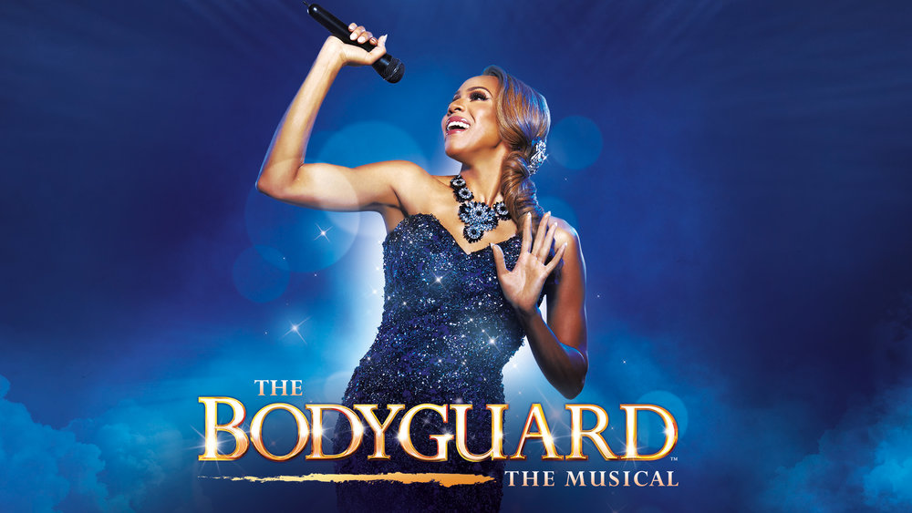 """Image description: Rachel Marron (Deborah Cox) smiles and belts into a microphone in her raised right hand. Seen from the waist up, she wears a strapless dress of shimmering beaded navy blue against a bright blue background. At the bottom, gold text reads: """"The Bodyguard"""" The Musical."""