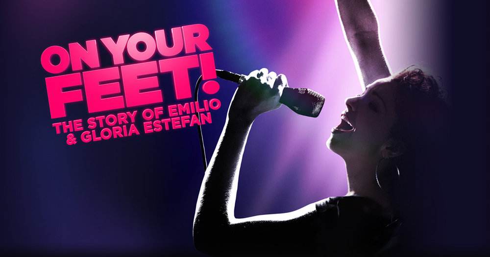 """Image description: Background of dark purple, at right a pink light glows behind a woman in profile, her face upturned and singing into a hand held microphone while she raises her other hand in the air. Text at left on a shallow diagonal and berry pink color reads """"On Your Feet! The Story of Emilio & Gloria Estefan""""."""