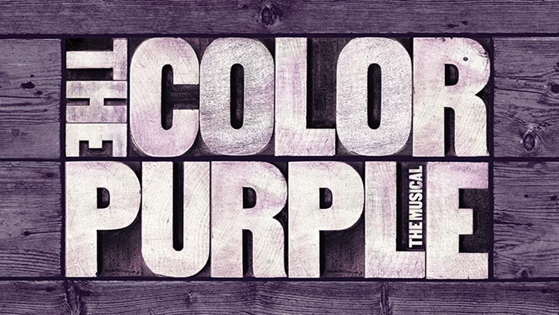 """Image Description: The Color Purple production logo, graphic: Background of purple hardwood planks placed horizontal, inset in boards is white wash text """"The Color Purple: The Musical""""."""