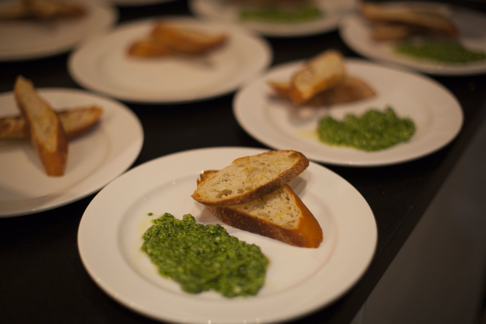 Second Course: Crostini, with Arugula Pesto, Marcona Almonds, and White Truffle Oil, found on page 42 in   The Vermont Non-GMO Cookbook  .