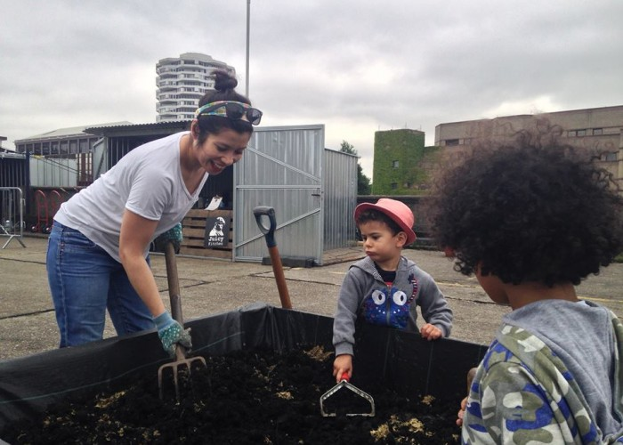 Joyce building raised beds on a rooftop Cinema shared garden, with the help of some young volunteers.