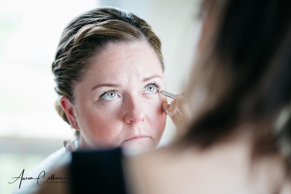Bride getting eyeliner applied by Lisa George during preparations.
