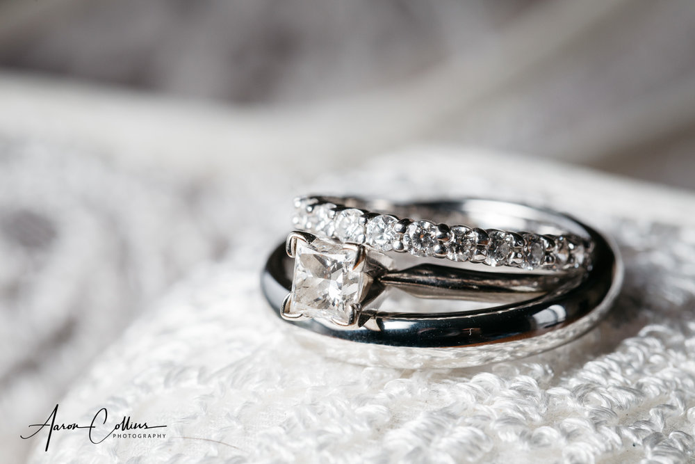 The wedding rings and diamond engagement ring close-up on top of the bride's white shoes.