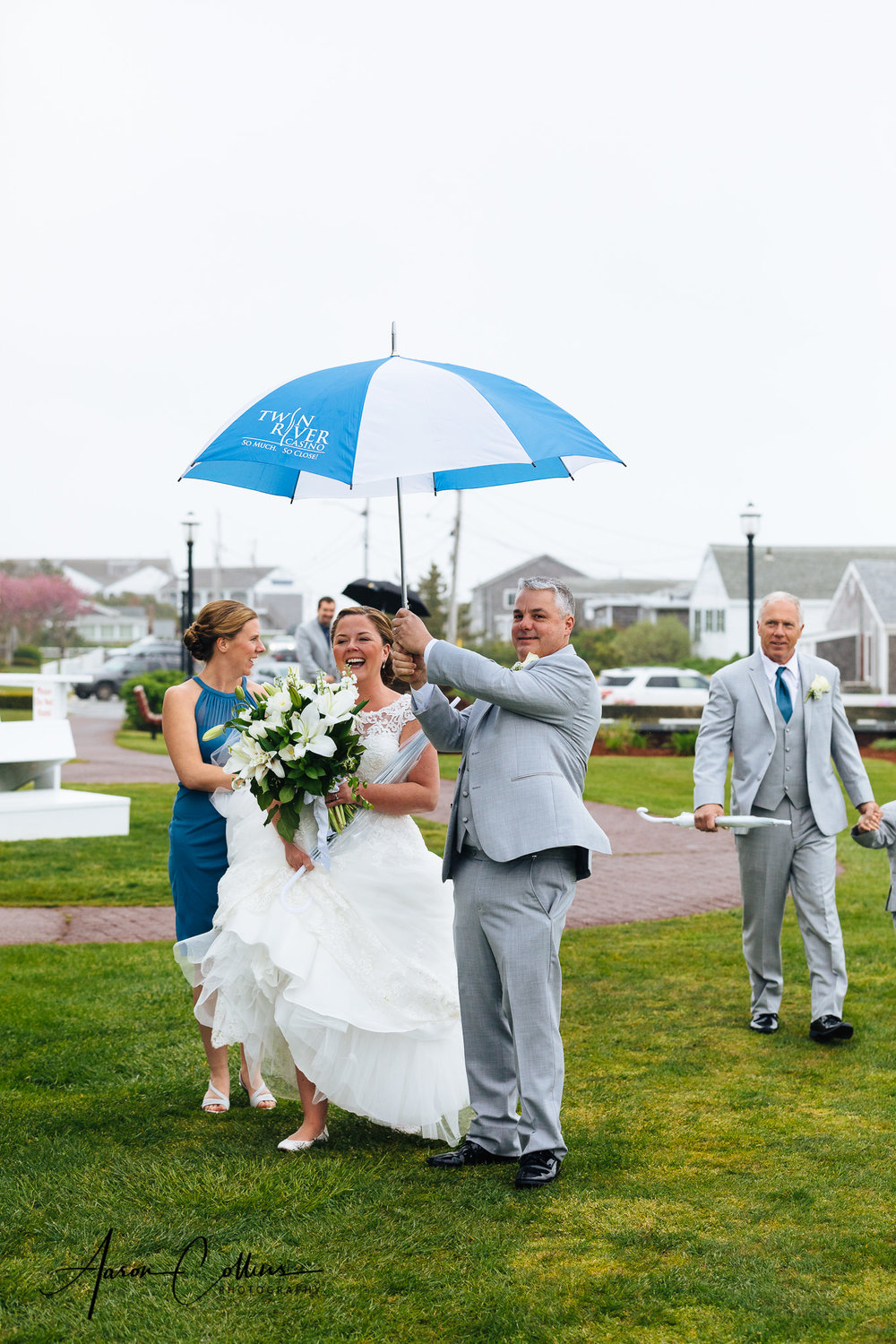 Bride staying dry under an umbrella while holding her bouquet on the way to her ceremony