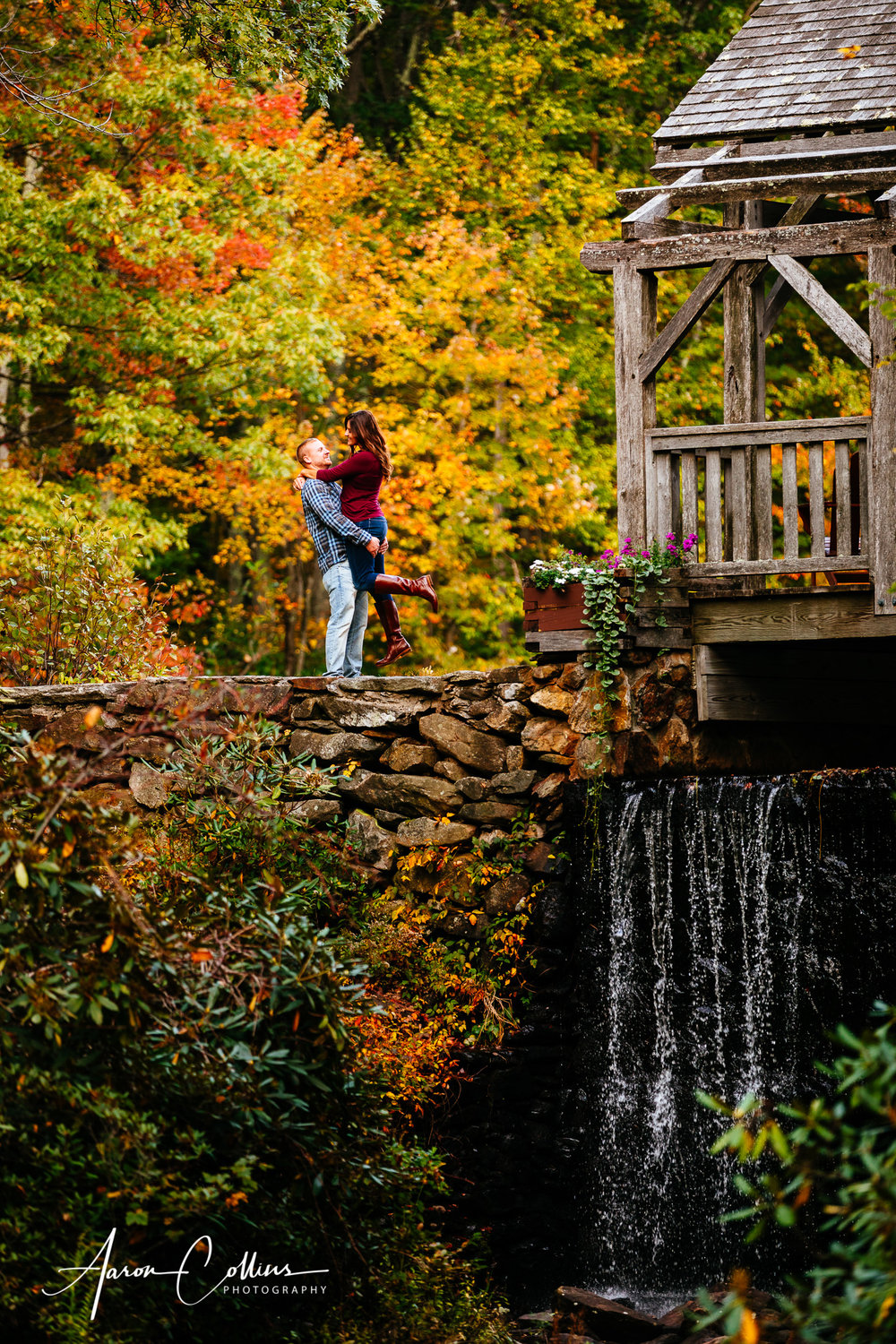 Fiance and bride to be standing over waterfall surrounded by fall foliage at Moore State Park for a New England engagement session.