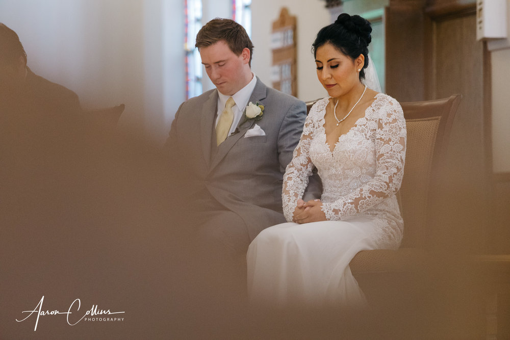 Bride and groom bowing in prayer during their catholic wedding ceremony at Saint George Parish in Worcester MA