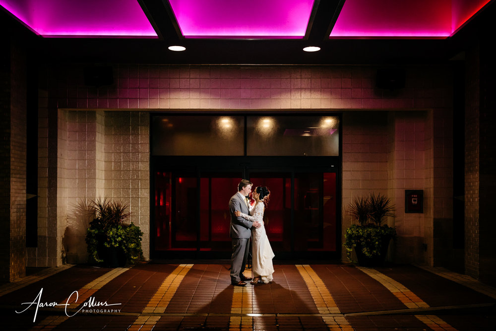 Creative night portrait of bride and groom outside the entrance to Verve Crown Plaza in Natick MA at their wedding reception.