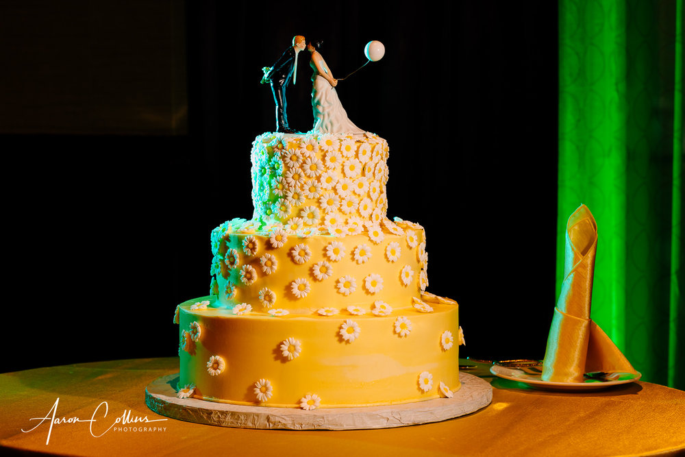 Wedding cake with flowery pattern and yellow frosting and topper with balloon with creative off-camera lighting using magmod at wedding reception at Verve Crown Plaza in Natick MA.