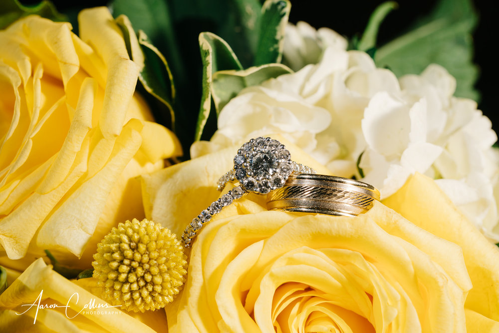 Close up of wedding rings and engagement ring in the yellow bouquet.
