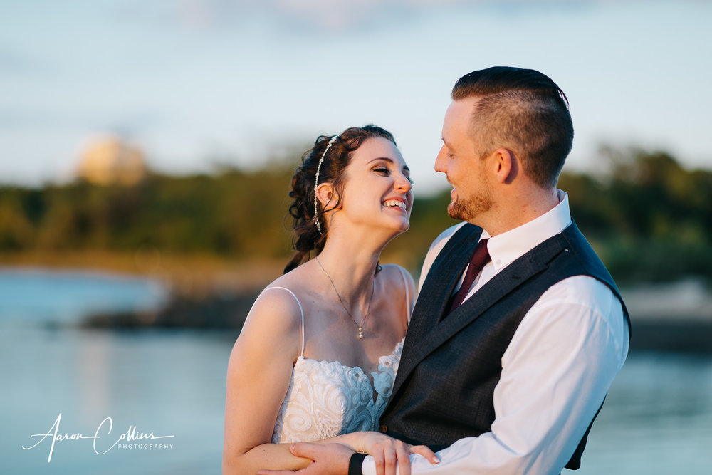 Bride and groom laughing during a portrait outside as the sun sets during golden hour on Block Island in the back yard of BIMI.