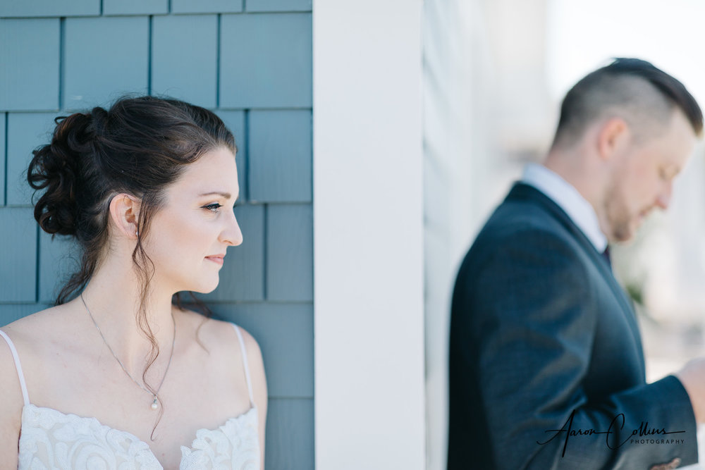 Bride waiting around the corner while her husband to be opens his gifts.