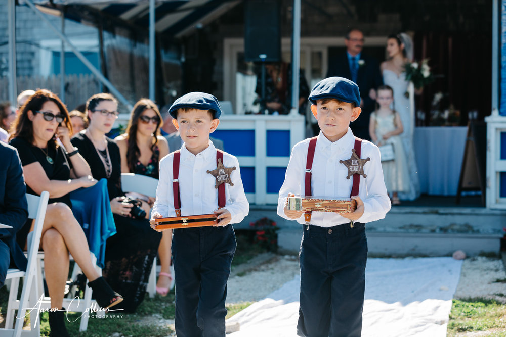 """The ring bearers, wearing """"ring security"""" badges as they dress in prohibition era costumes walking down the aisle."""
