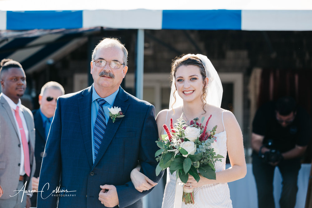 Father walks his daughter, the bride down the aisle.