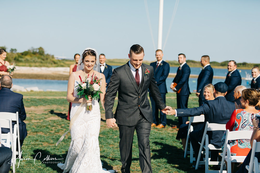 Groom reaches out and touches his father's hand during the recessional at Block Island Maritime Institute.