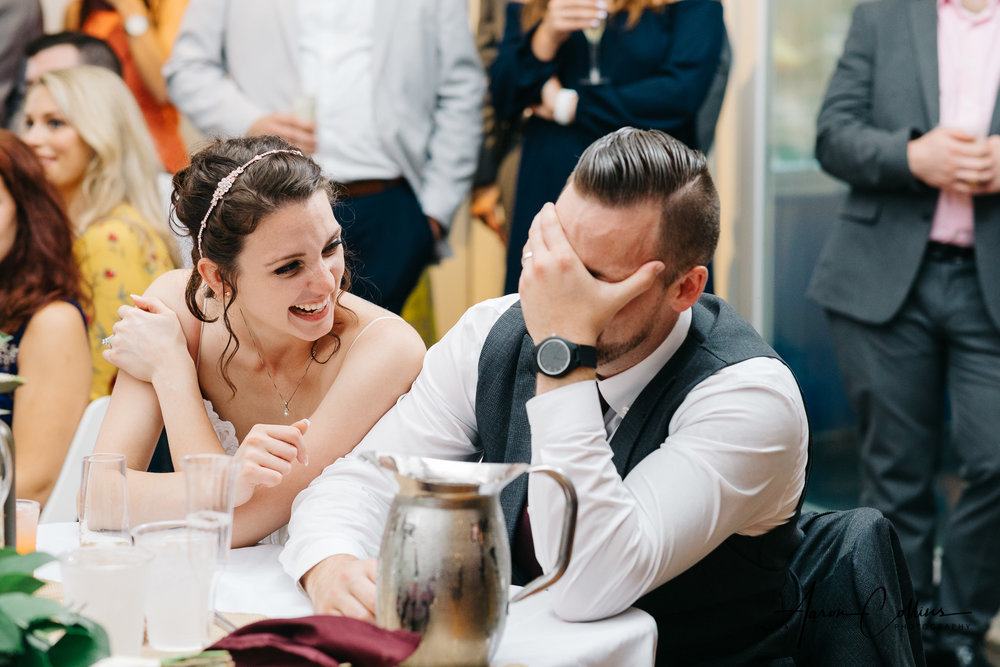Groom covering his face reacting to the toast from best man while bride laughs at Block Island Maritime Institute
