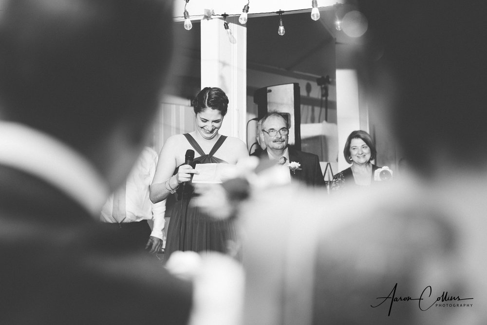 View through the shoulders of bride and groom of Maid of honor giving her toast in black and white at block island maritime institute