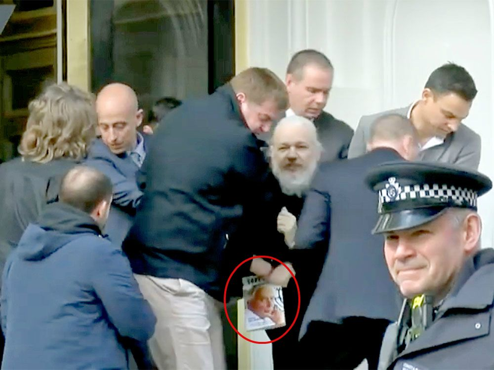 ( National Post ) Julian Assange, seen clutching a book by Gore Vidal, is dragged away from the Ecuadorian embassy. RUPTLY