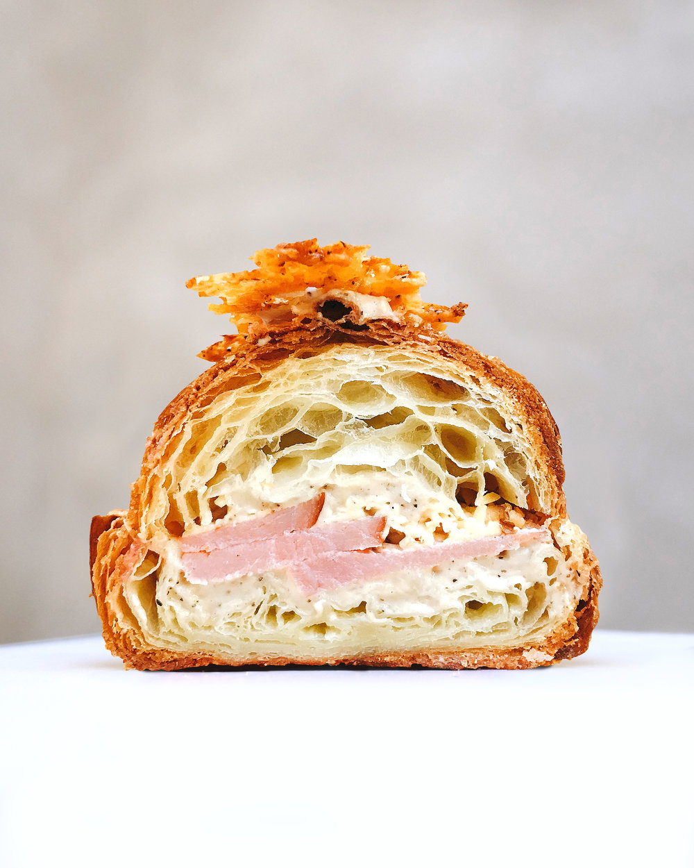 Ham & Cheese Twice Baked $8 - Thick cut smoked ham, Gouda cheese, cheddar cheese and a super creamy béchamel sauce baked in our classic croissant and then topped with crispy cheese shards.