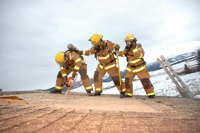 Fort Ellis volunteers practice venting a roof during a training exercise.
