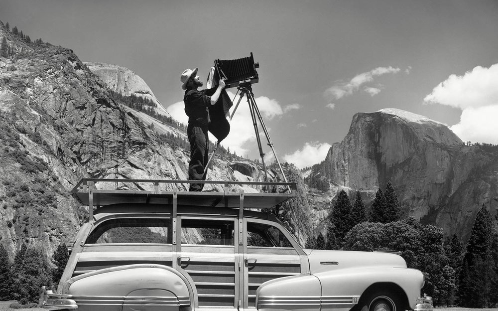 Ansel Adams using his woody wagon as a platform to set up a shoot in Yosemite National Park.