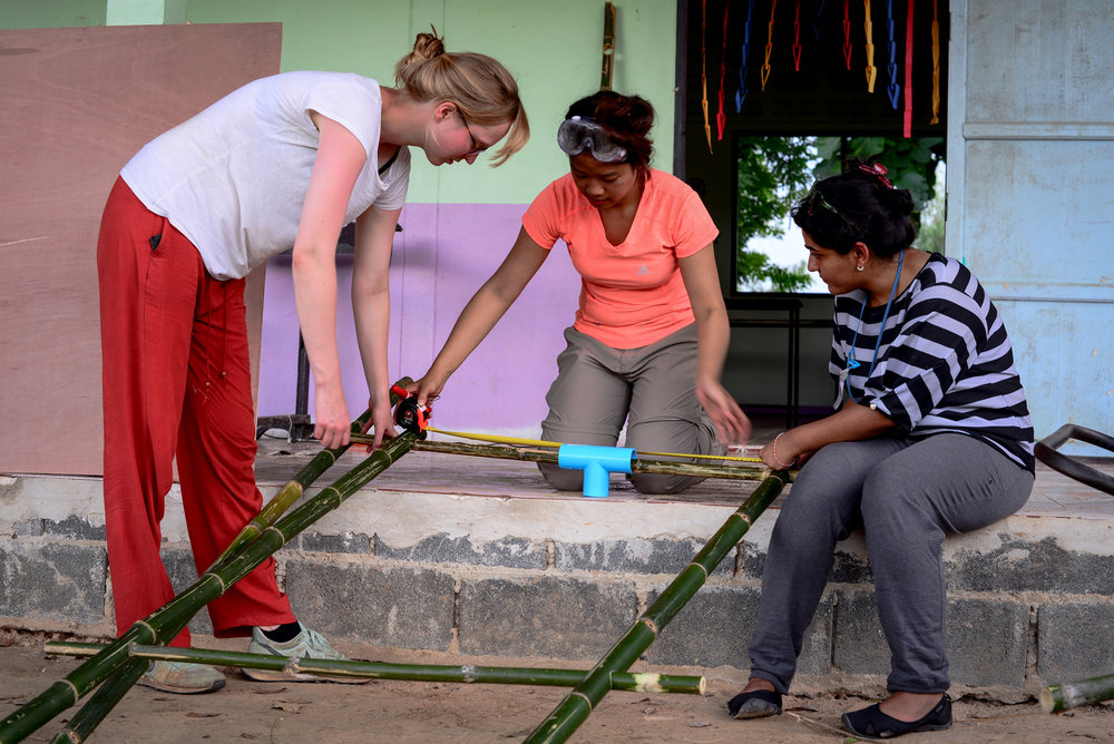 Franzi from Germany, Mint from Thailand, and Mansi from India at IDDS Sisaket in July 2017 building flipchart holders from local materials in rural Thailand. photo credit. Kendra Sharp