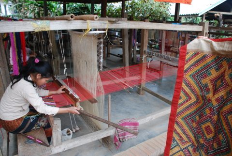 Woman Making Fabric with a massive weaving loom in Asia