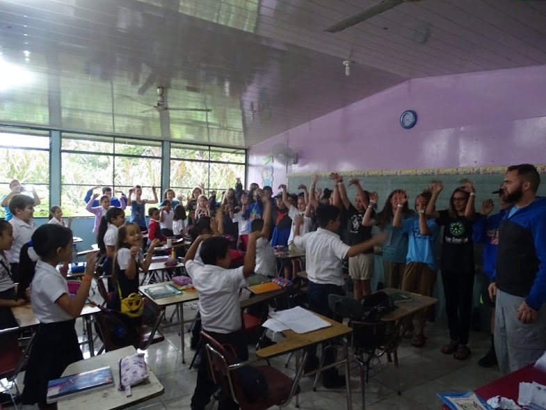 This was our service learning project at a school in Sarapiqui. We were teaching them a repeat- after-me song. We taught them the movements and the words; they were quickly able to figure out the song. We also tried to learn their names and talk to them in their native language. We helped spread the word about no bullying by painting in a mural and painting barrels with that message.   Words by Priest Muniz, photo by Julie Israelson.