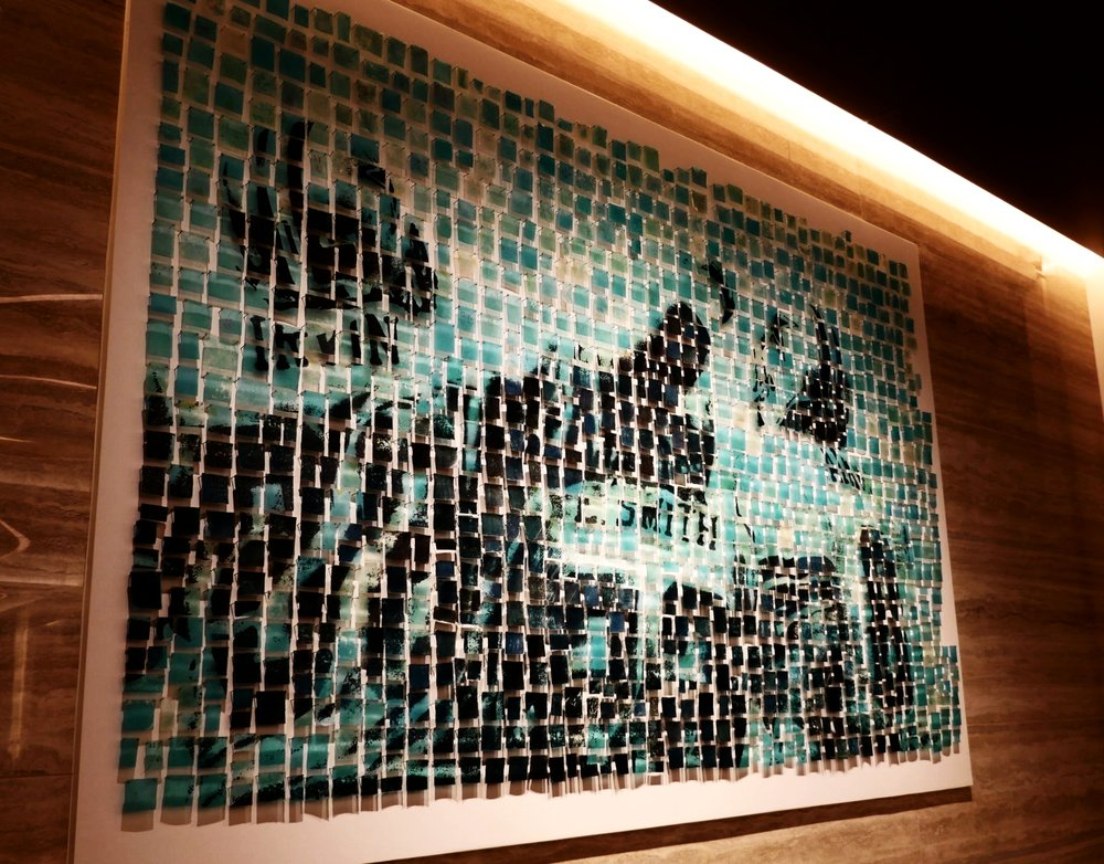 "Using the ""End of Days"" image provided by the Dallas Cowboys Archives, Brandie Grogan of Kalisher created the art installation behind the reception desk, a collage of green- and blue-hued resin squares."